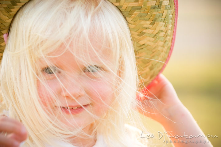 girl with blue eyes and straw hat smiling. wind blowing her hair. Kent Island, Annapolis Maryland candid children lifestyle portrait photo at beach and farm
