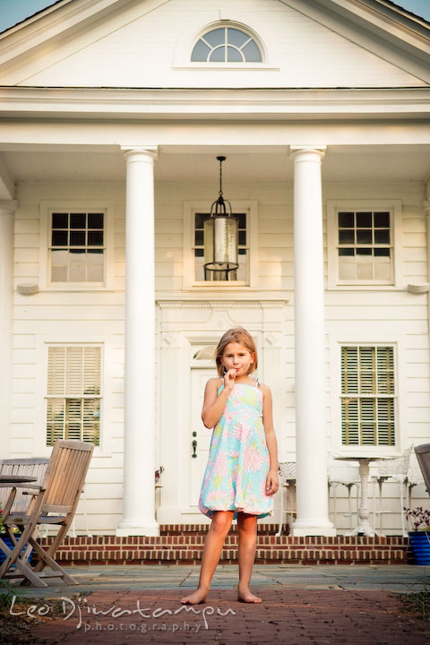 Little girl in pastel flower summer dress eating lollipop in front of an old victorian style building. Kent Island, Annapolis Maryland candid children lifestyle portrait photo at beach and farm