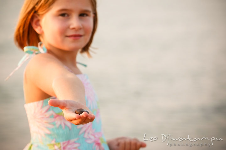 A girl showing a smooth pebble she found on the beach. Kent Island, Annapolis Maryland candid children lifestyle portrait photo at beach and farm