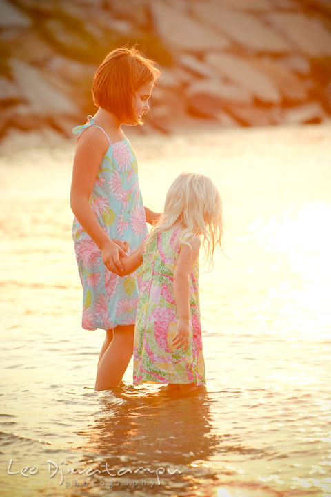 Two sisters wading in the water on the beach at sunset. Kent Island, Annapolis Maryland candid children lifestyle portrait photo at beach and farm