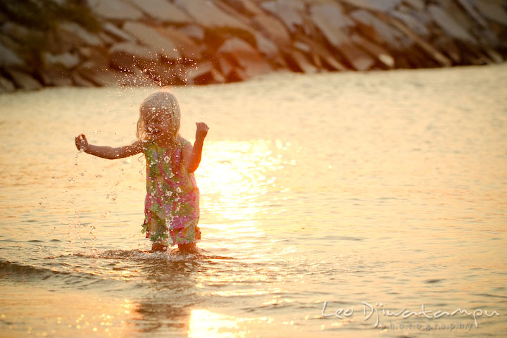 Toddler girl playing and splashing water on the beach at sunset. Kent Island, Annapolis Maryland candid children lifestyle portrait photo at beach and farm