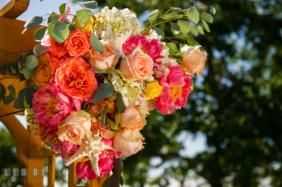 Peonies and roses flower arrangement for the ceremonial arch by florist Intrigue Design and Decor. Kent Island Maryland Chesapeake Bay Beach Club wedding photo, by wedding photographers of Leo Dj Photography. http://leodjphoto.com
