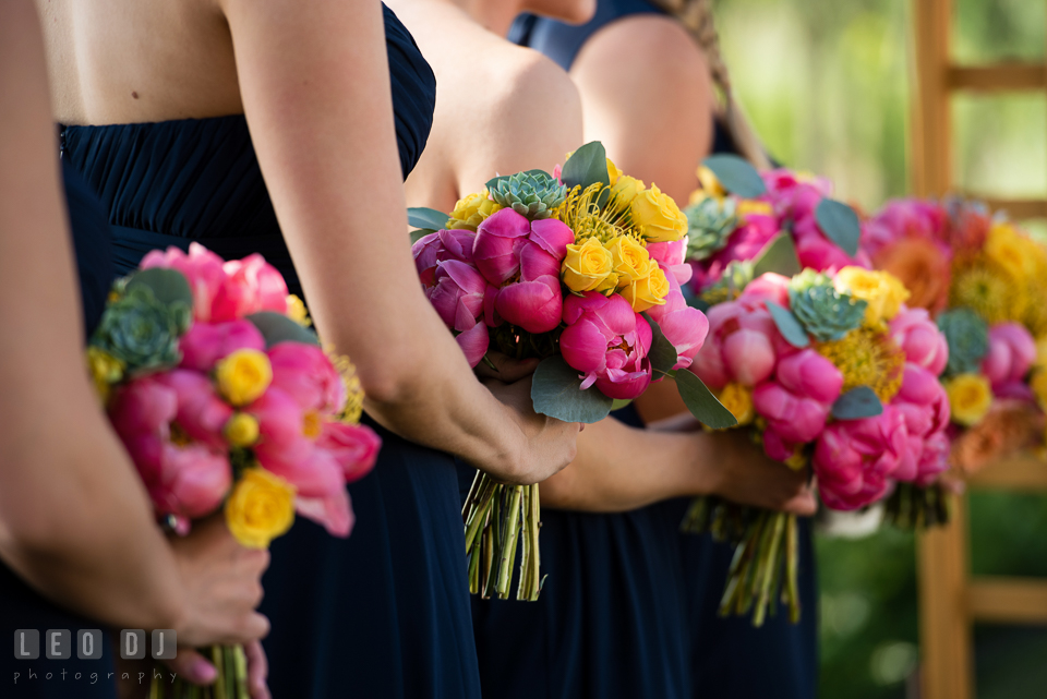 Bridesmaids during the ceremony holding their pink and yellow flower bouquets by florist Intrigue Design and Decor. Kent Island Maryland Chesapeake Bay Beach Club wedding photo, by wedding photographers of Leo Dj Photography. http://leodjphoto.com