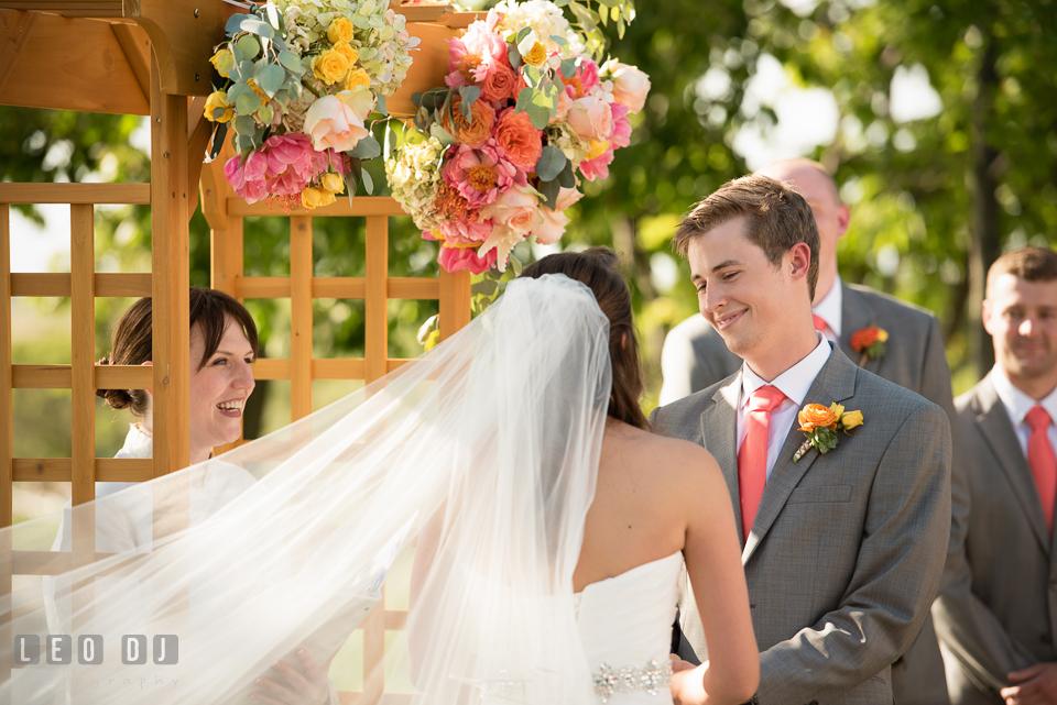 Groom smiling looking at Bride while reciting wedding vows. Kent Island Maryland Chesapeake Bay Beach Club wedding photo, by wedding photographers of Leo Dj Photography. http://leodjphoto.com
