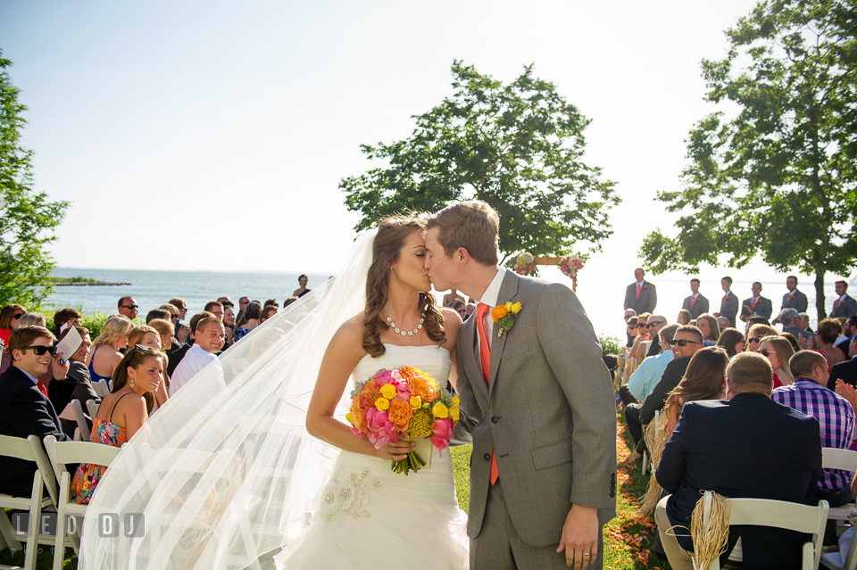 Bride and Groom kissing as the walk out of the aisle after the ceremony. Kent Island Maryland Chesapeake Bay Beach Club wedding photo, by wedding photographers of Leo Dj Photography. http://leodjphoto.com