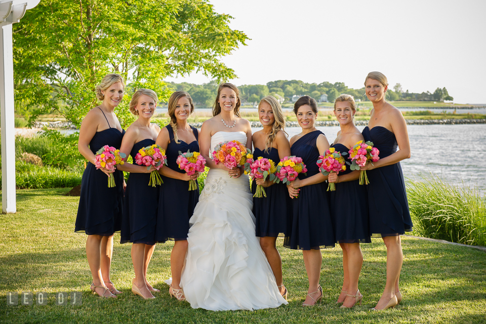 Bride, Matron of Honor, and Bridesmaids holding large flower bouquets by florist Intrigue Design and Decor. Kent Island Maryland Chesapeake Bay Beach Club wedding photo, by wedding photographers of Leo Dj Photography. http://leodjphoto.com