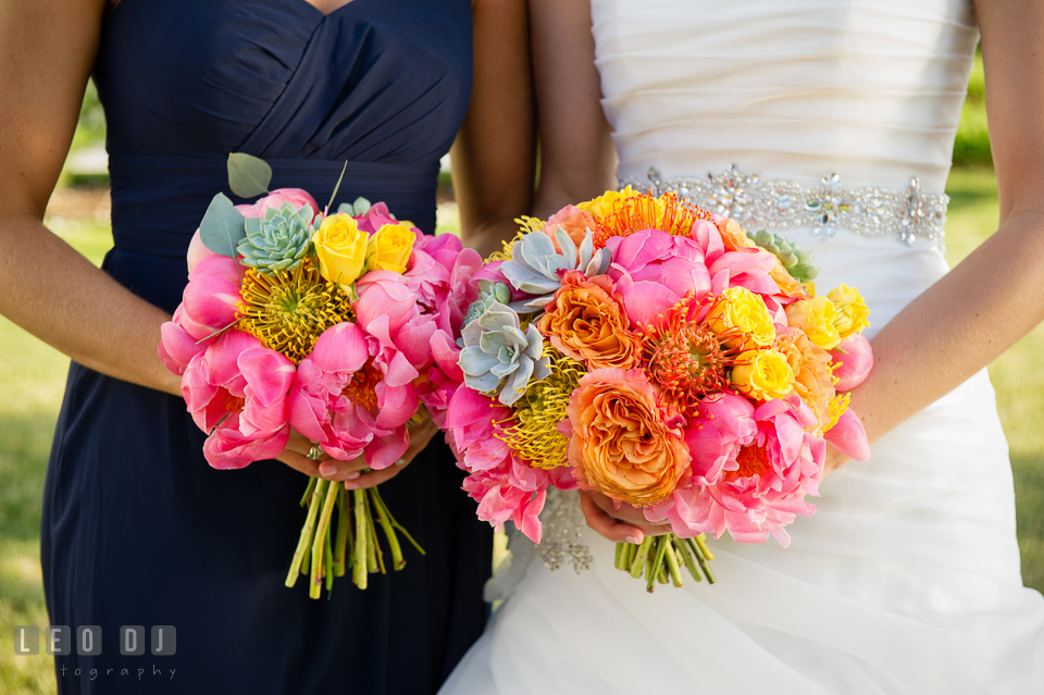 Bride and Matron of Honor holding flower bouquet of pink peonies, with orange and yellow roses, and succulents designed by florist Intrigue Design and Decor. Kent Island Maryland Chesapeake Bay Beach Club wedding photo, by wedding photographers of Leo Dj Photography. http://leodjphoto.com