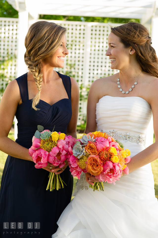 Bride and Matron of Honor looking at each other smiling while holding floral bouquet by florist Intrigue Design and Decor. Kent Island Maryland Chesapeake Bay Beach Club wedding photo, by wedding photographers of Leo Dj Photography. http://leodjphoto.com