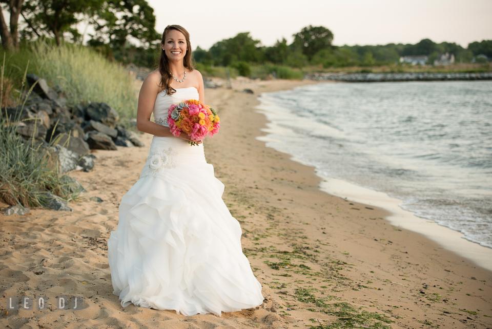 Bride posing on the beach holding gorgeous floral bouquet by florist Intrigue Design and Decor. Kent Island Maryland Chesapeake Bay Beach Club wedding photo, by wedding photographers of Leo Dj Photography. http://leodjphoto.com