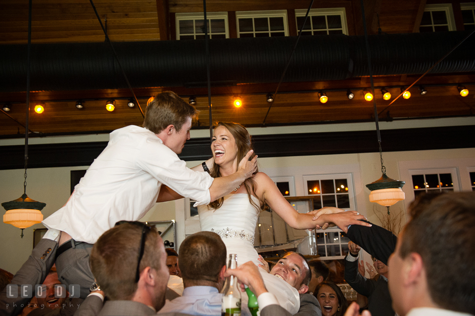 Bride and Groom about to kiss as they were lifted up high by the guests. Kent Island Maryland Chesapeake Bay Beach Club wedding photo, by wedding photographers of Leo Dj Photography. http://leodjphoto.com