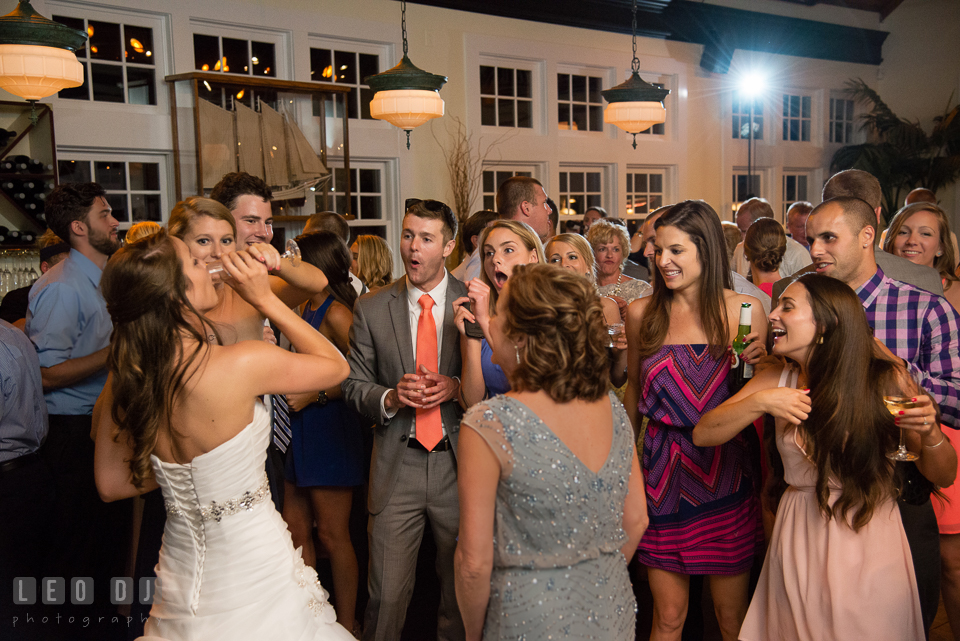 Bridesmaid help Bride drink while guests observing in awe. Kent Island Maryland Chesapeake Bay Beach Club wedding photo, by wedding photographers of Leo Dj Photography. http://leodjphoto.com