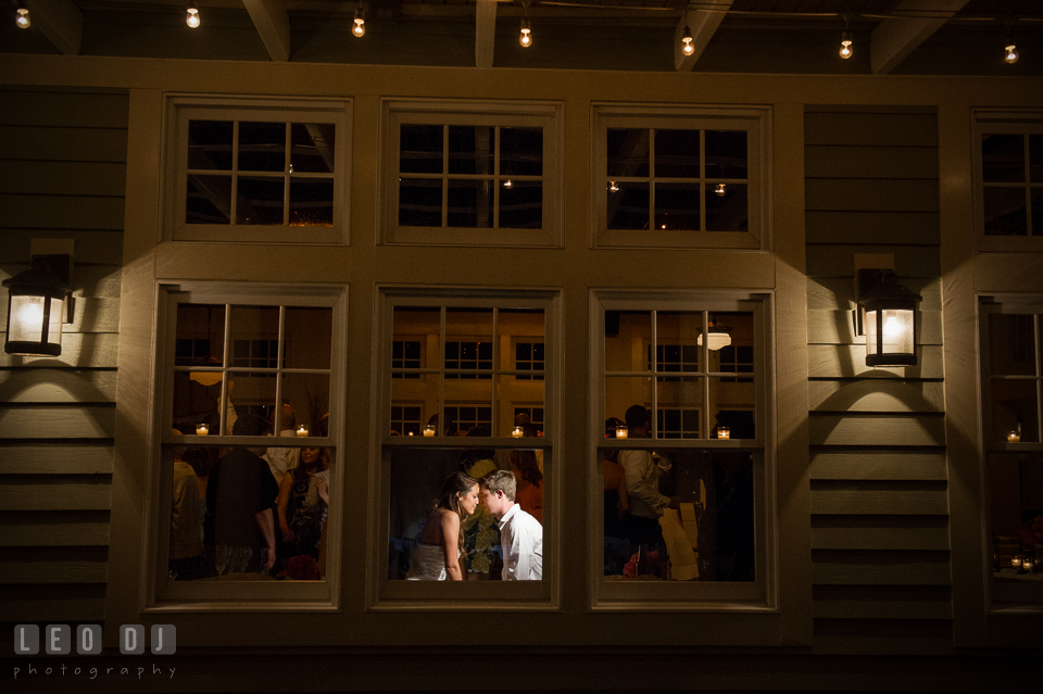 Bride and Groom touching heads inside reception hall seen from window outside. Kent Island Maryland Chesapeake Bay Beach Club wedding photo, by wedding photographers of Leo Dj Photography. http://leodjphoto.com