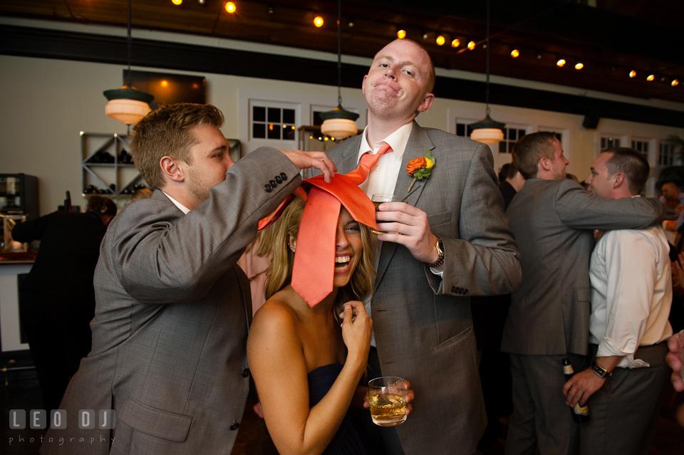 Groomsmen put their ties on Bridesmaid's head. Kent Island Maryland Chesapeake Bay Beach Club wedding photo, by wedding photographers of Leo Dj Photography. http://leodjphoto.com