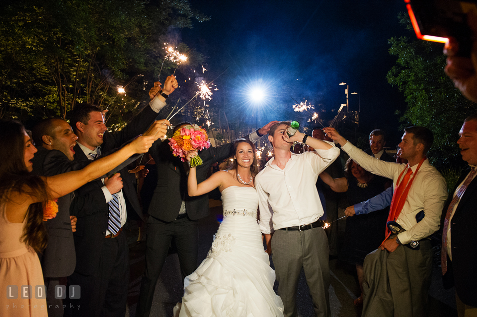 Bride and Groom cheered as they exit the venue with guests holding sparklers. Kent Island Maryland Chesapeake Bay Beach Club wedding photo, by wedding photographers of Leo Dj Photography. http://leodjphoto.com