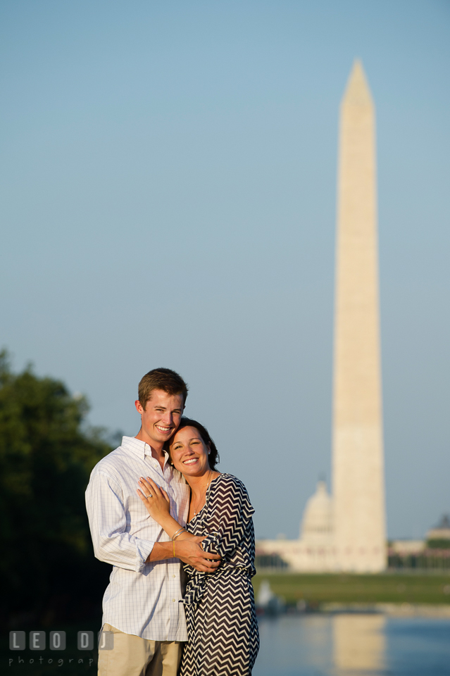 Engaged couple hugging and posing in front of the Monument and the Capitol Building. Washington DC pre-wedding engagement photo session at Lincoln Memorial, by wedding photographers of Leo Dj Photography. http://leodjphoto.com