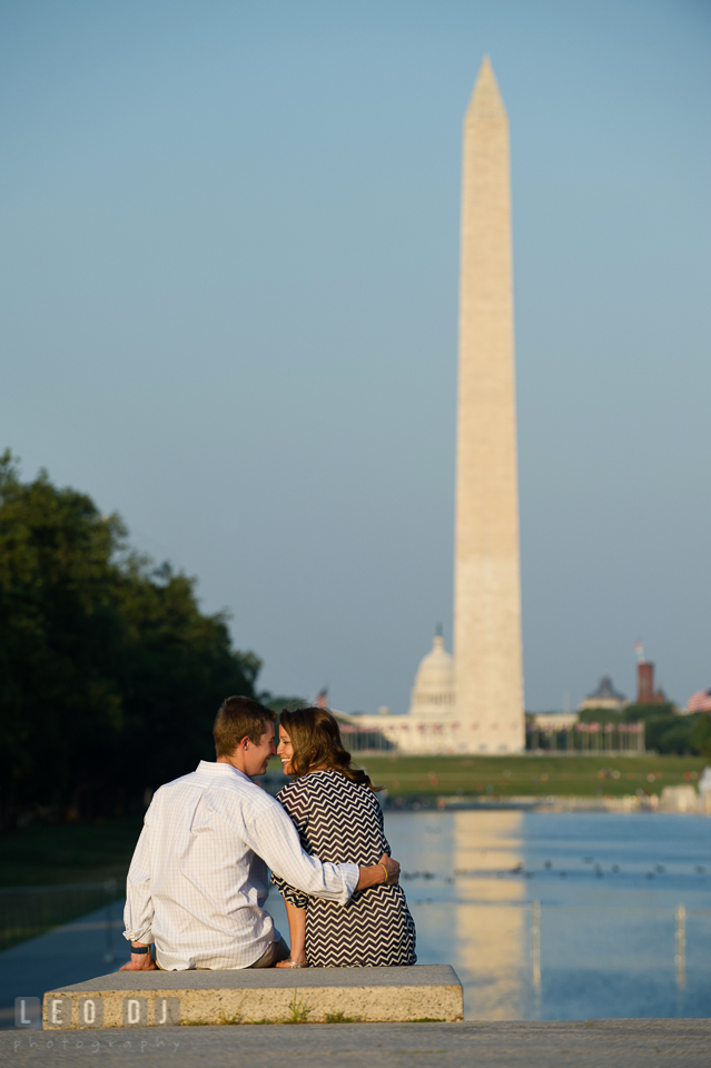 Engaged guy sitting close to his fiancée by the reflecting pool. Washington DC pre-wedding engagement photo session at Lincoln Memorial, by wedding photographers of Leo Dj Photography. http://leodjphoto.com