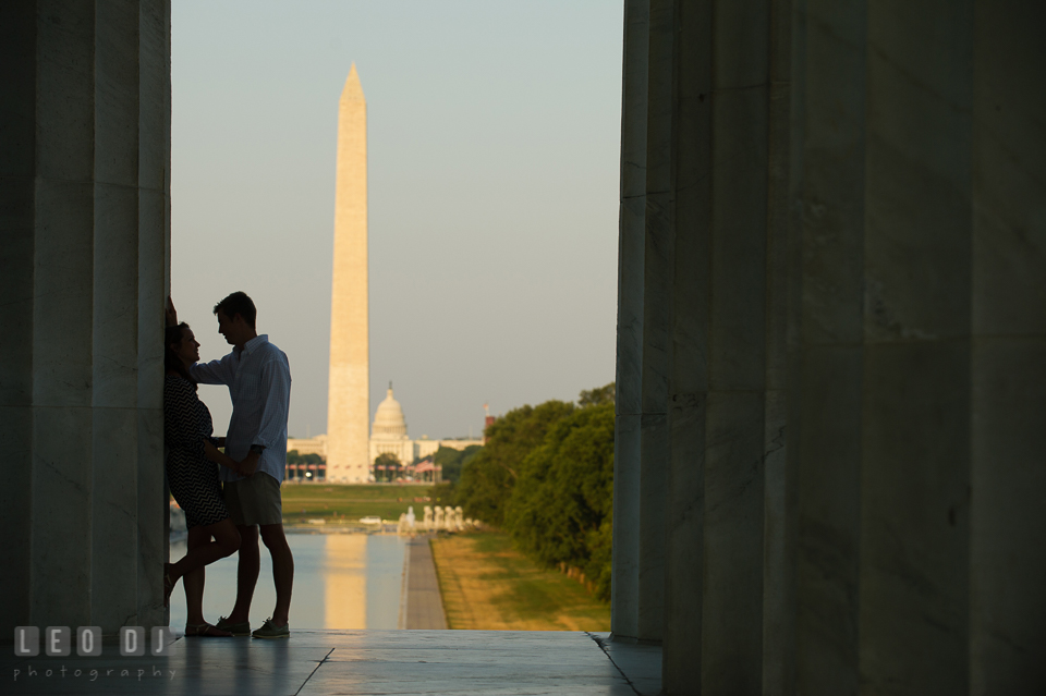 Engaged girl leaning on column, and fiancé about to kiss. Washington Monument, Capitol and reflecting pool in the background. Washington DC pre-wedding engagement photo session at Lincoln Memorial, by wedding photographers of Leo Dj Photography. http://leodjphoto.com