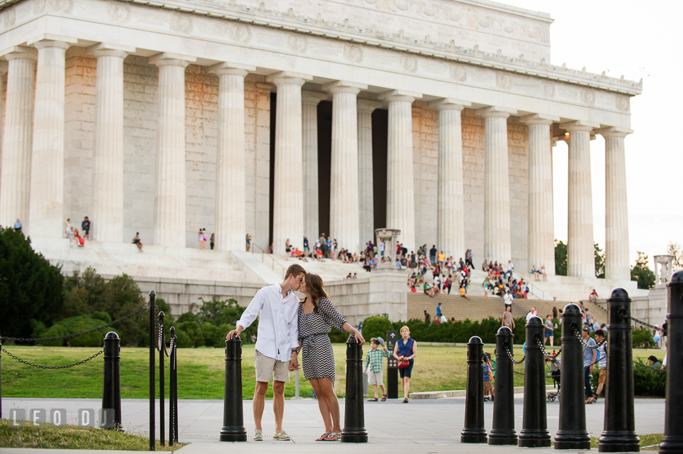 Engaged guy and girl kissing in front of the Abraham Lincoln Memorial. Washington DC pre-wedding engagement photo session at Lincoln Memorial, by wedding photographers of Leo Dj Photography. http://leodjphoto.com