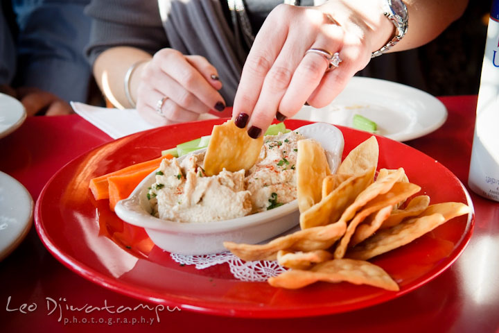 Engaged girl with diamond engagement ring dipping chips. Pre-wedding Engagement Photo Session Federal Hill Baltimore and Mother's Grille restaurant bar by wedding photographer Leo Dj Photography