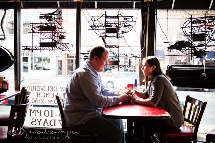 A guy and his fiancée sitting and holding hands. Pre-wedding Engagement Photo Session Federal Hill Baltimore and Mother's Grille restaurant bar by wedding photographer Leo Dj Photography