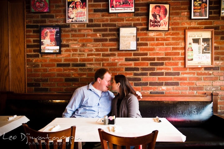 Engaged guy cuddling with his fiancée in a restaurant. Pre-wedding Engagement Photo Session Federal Hill Baltimore and Mother's Grille restaurant bar by wedding photographer Leo Dj Photography