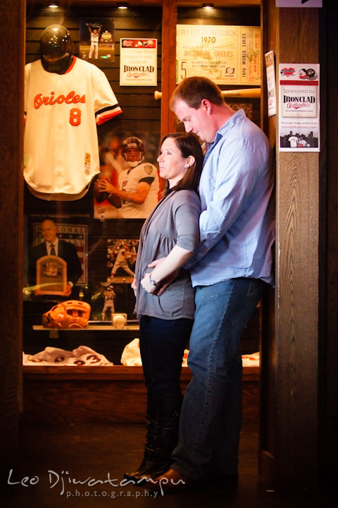Engaged guy hugging his fiancée by the Orioles jersey display. Pre-wedding Engagement Photo Session Federal Hill Baltimore and Mother's Grille restaurant bar by wedding photographer Leo Dj Photography