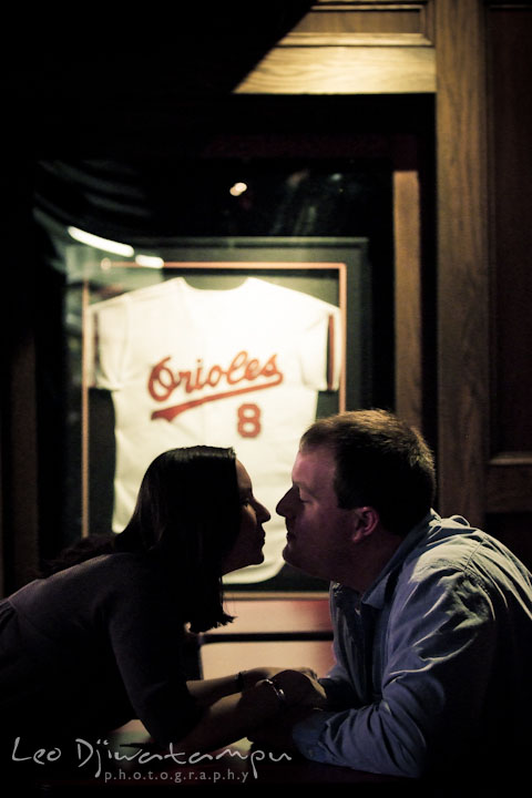 Engaged girl almost kissed her fiancé with Orioles jersey display in the background. Pre-wedding Engagement Photo Session Federal Hill Baltimore and Mother's Grille restaurant bar by wedding photographer Leo Dj Photography