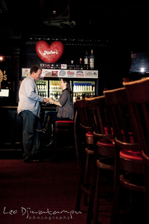 Engaged girl talking to her fiancé in a bar. Pre-wedding Engagement Photo Session Federal Hill Baltimore and Mother's Grille restaurant bar by wedding photographer Leo Dj Photography