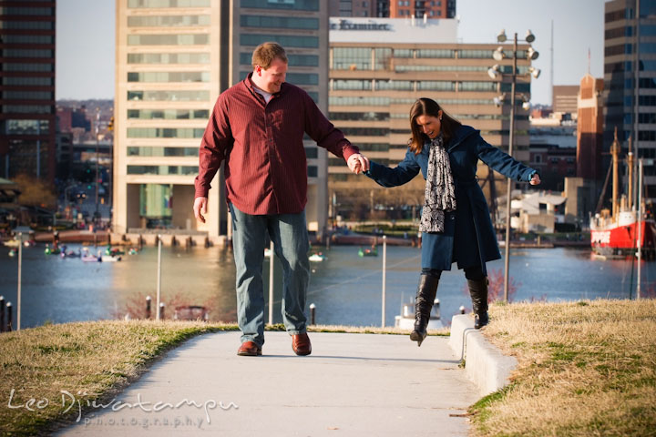 Engaged guy and girl walking, laughing with city view of high rise building. Pre-wedding Engagement Photo Session Federal Hill Baltimore and Mother's Grille restaurant bar by wedding photographer Leo Dj Photography