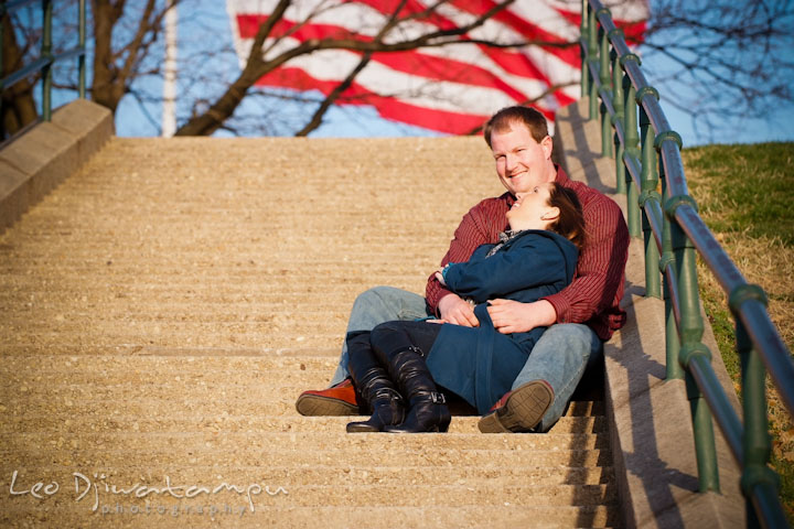 Engaged girl sitting and leaning on fiancé, laughing. American flag in the background. Pre-wedding Engagement Photo Session Federal Hill Baltimore and Mother's Grille restaurant bar by wedding photographer Leo Dj Photography