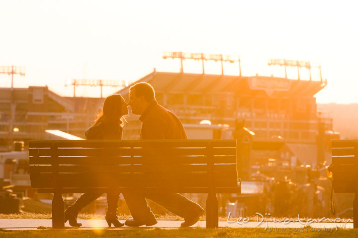 Engaged couple kissing in the sunset light, Ravens stadium in the background. Pre-wedding Engagement Photo Session Federal Hill Baltimore and Mother's Grille restaurant bar by wedding photographer Leo Dj Photography