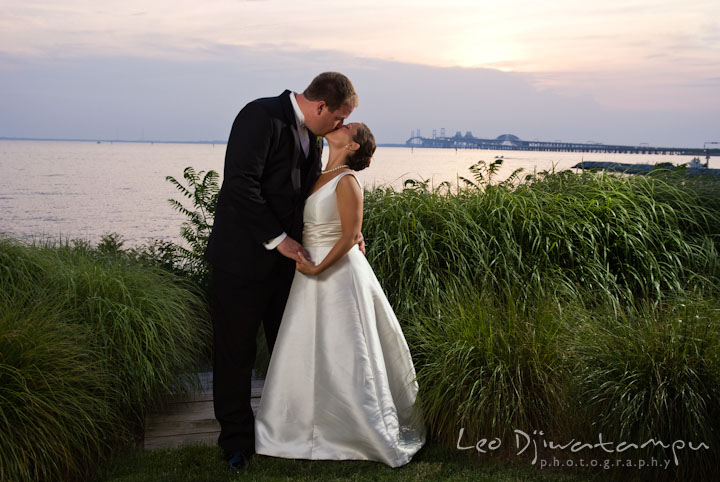 Bride and groom kissing with sunset on the chesapeake bay and bay bridge on the background. Chesapeake Bay Beach Club Wedding photos by photographers of Leo Dj Photography