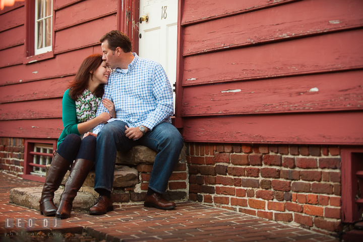 Engaged guy sitting in front of a rustic red house kissing his fiancée. Annapolis Eastern Shore Maryland pre-wedding engagement photo session at downtown, by wedding photographers of Leo Dj Photography. http://leodjphoto.com