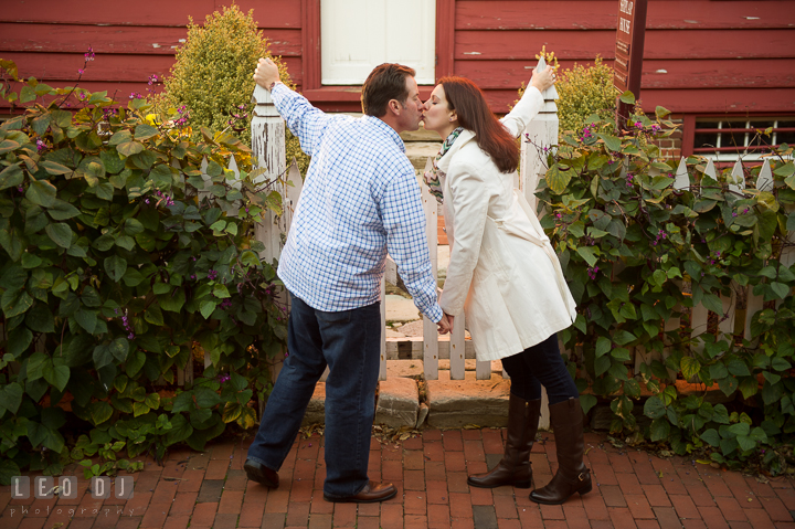 Engaged couple holding hands and kissing in front of a garden gate . Annapolis Eastern Shore Maryland pre-wedding engagement photo session at downtown, by wedding photographers of Leo Dj Photography. http://leodjphoto.com