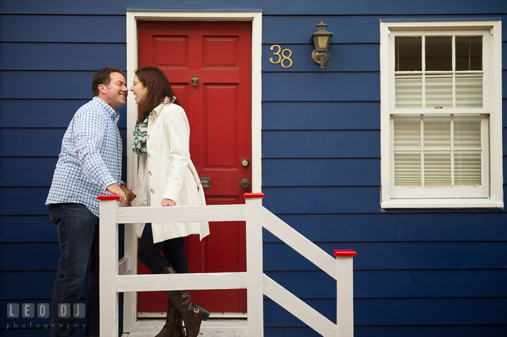 Engaged couple almost kissed in front of a rustic blue house with red door. Annapolis Eastern Shore Maryland pre-wedding engagement photo session at downtown, by wedding photographers of Leo Dj Photography. http://leodjphoto.com