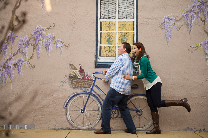 Engaged guy and his fiancée goofing around, pretending to ride a painting bicycle. Annapolis Eastern Shore Maryland pre-wedding engagement photo session at downtown, by wedding photographers of Leo Dj Photography. http://leodjphoto.com