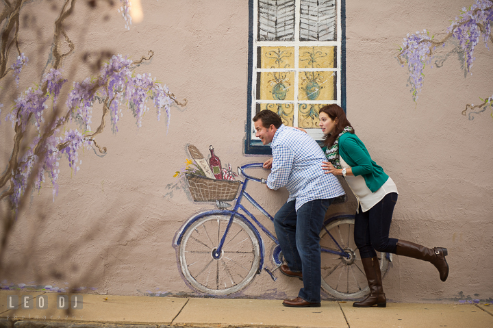 Engaged couple pretending to ride a painting bicycle. Annapolis Eastern Shore Maryland pre-wedding engagement photo session at downtown, by wedding photographers of Leo Dj Photography. http://leodjphoto.com