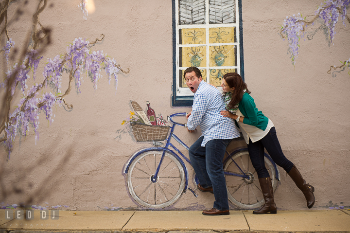 Engaged girl and her fiancé goofing around, pretending to ride a painting bicycle. Annapolis Eastern Shore Maryland pre-wedding engagement photo session at downtown, by wedding photographers of Leo Dj Photography. http://leodjphoto.com