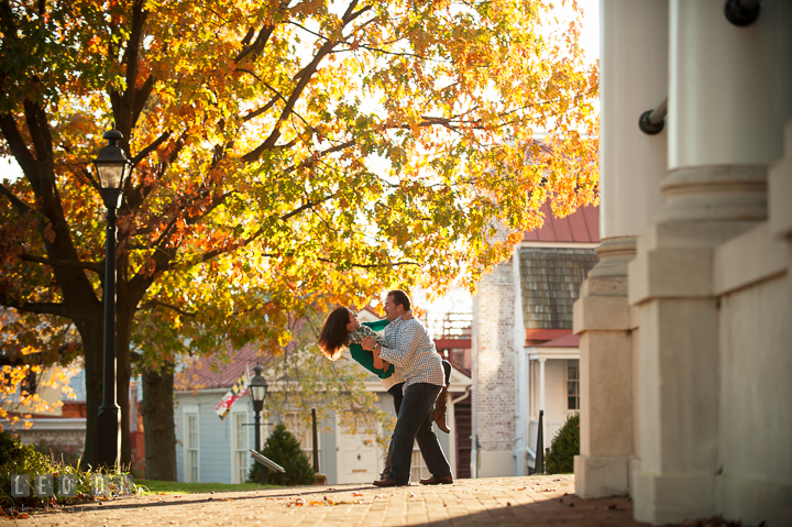 Engaged couple dancing and doing the dip under a yellow foliage tree in autumn. Annapolis Eastern Shore Maryland pre-wedding engagement photo session at downtown, by wedding photographers of Leo Dj Photography. http://leodjphoto.com