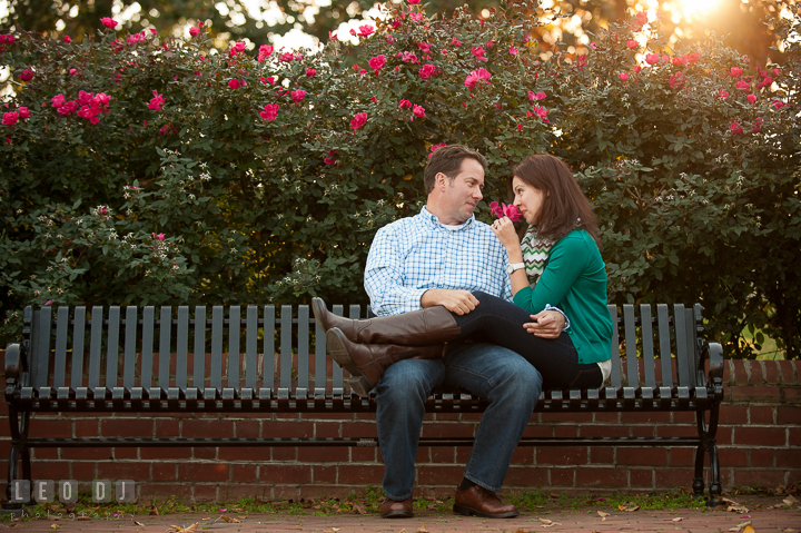 Engaged girl sitting on a bench with her fiancé smelling red rose. Annapolis Eastern Shore Maryland pre-wedding engagement photo session at downtown, by wedding photographers of Leo Dj Photography. http://leodjphoto.com