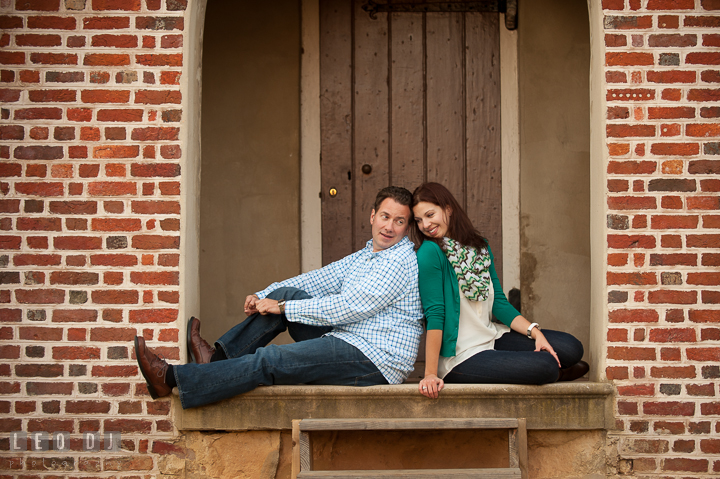 Engaged couple leaning their backs against each other under a brick building arch. Annapolis Eastern Shore Maryland pre-wedding engagement photo session at downtown, by wedding photographers of Leo Dj Photography. http://leodjphoto.com