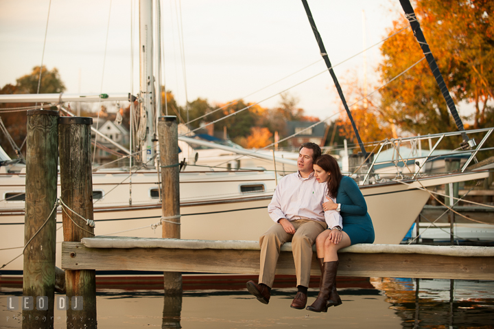 Engaged couple cuddling on a boat dock at Eastport with fall foliage in the background. Annapolis Eastern Shore Maryland pre-wedding engagement photo session at downtown, by wedding photographers of Leo Dj Photography. http://leodjphoto.com