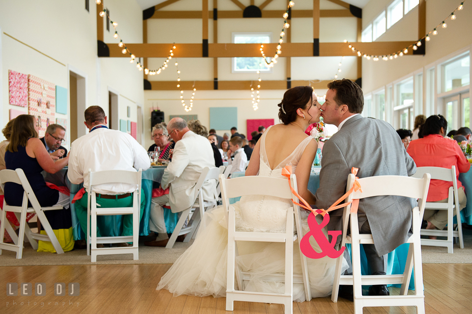 Bride and Groom kissing at the sweetheart table during the reception dinner. Chesapeake Bay Environmental Center, Eastern Shore Maryland, wedding reception and ceremony photo, by wedding photographers of Leo Dj Photography. http://leodjphoto.com