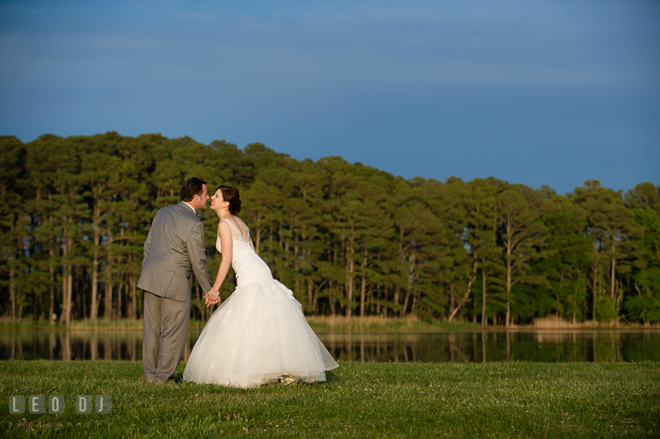 Bride and Groom standing and holding hands beside the beautiful lake. Chesapeake Bay Environmental Center, Eastern Shore Maryland, wedding reception and ceremony photo, by wedding photographers of Leo Dj Photography. http://leodjphoto.com