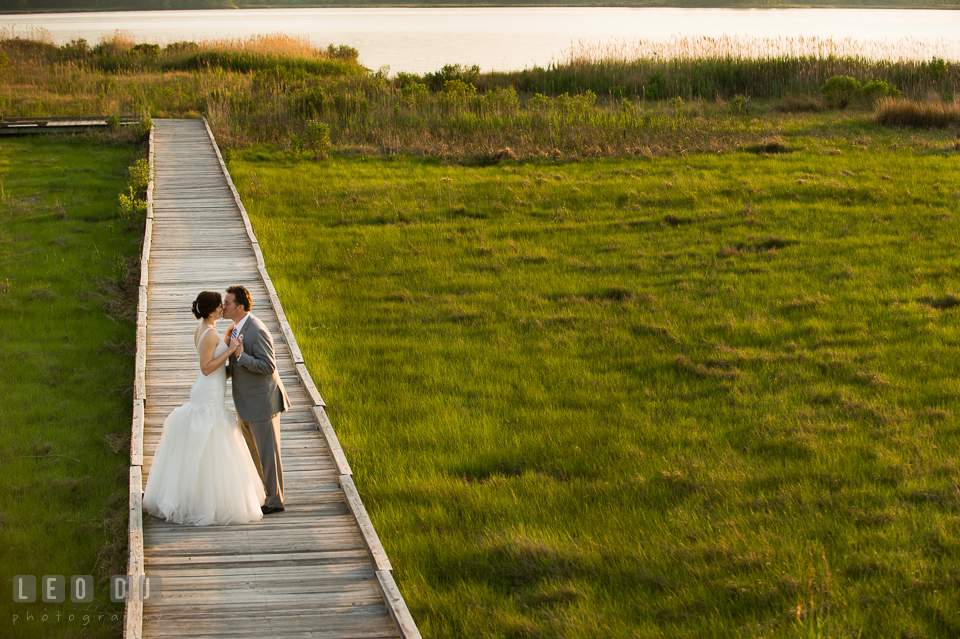 Bride and Groom kissing on the boardwalk by the beach. Chesapeake Bay Environmental Center, Eastern Shore Maryland, wedding reception and ceremony photo, by wedding photographers of Leo Dj Photography. http://leodjphoto.com