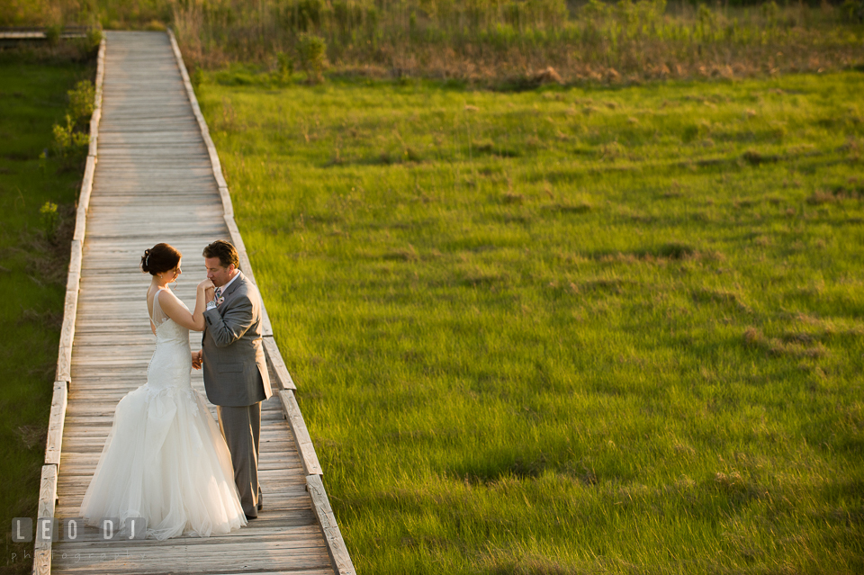 Groom kissing Bride's hand on the boardwalk at the beach. Chesapeake Bay Environmental Center, Eastern Shore Maryland, wedding reception and ceremony photo, by wedding photographers of Leo Dj Photography. http://leodjphoto.com