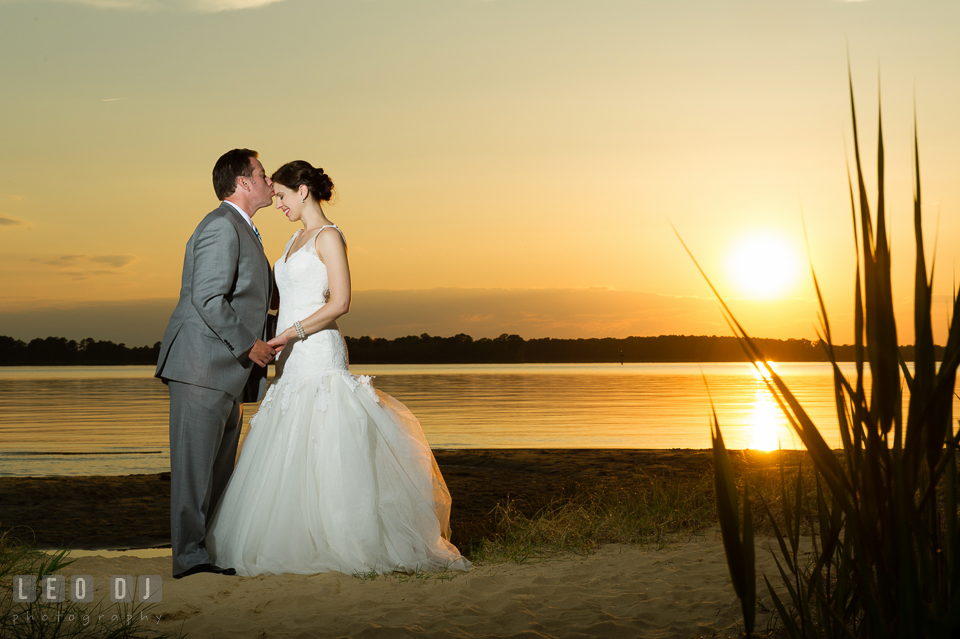 Groom kissing Bride during sunset on the beach. Chesapeake Bay Environmental Center, Eastern Shore Maryland, wedding reception and ceremony photo, by wedding photographers of Leo Dj Photography. http://leodjphoto.com