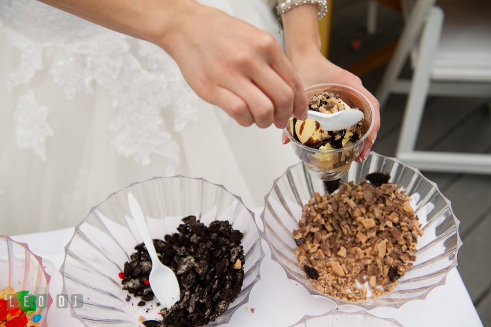 Bride sprinkles topping on delicious ice cream from Scottish Highland Creamery Sundae Bar. Chesapeake Bay Environmental Center, Eastern Shore Maryland, wedding reception and ceremony photo, by wedding photographers of Leo Dj Photography. http://leodjphoto.com