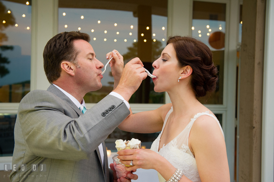 The Bride and Groom sharing scoops of ice cream from Scottish Highland Creamery Sundae Bar. Chesapeake Bay Environmental Center, Eastern Shore Maryland, wedding reception and ceremony photo, by wedding photographers of Leo Dj Photography. http://leodjphoto.com