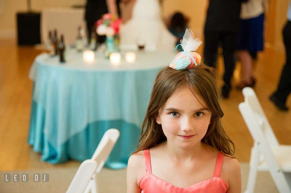 Flower girl balancing wedding favor on her head. Chesapeake Bay Environmental Center, Eastern Shore Maryland, wedding reception and ceremony photo, by wedding photographers of Leo Dj Photography. http://leodjphoto.com